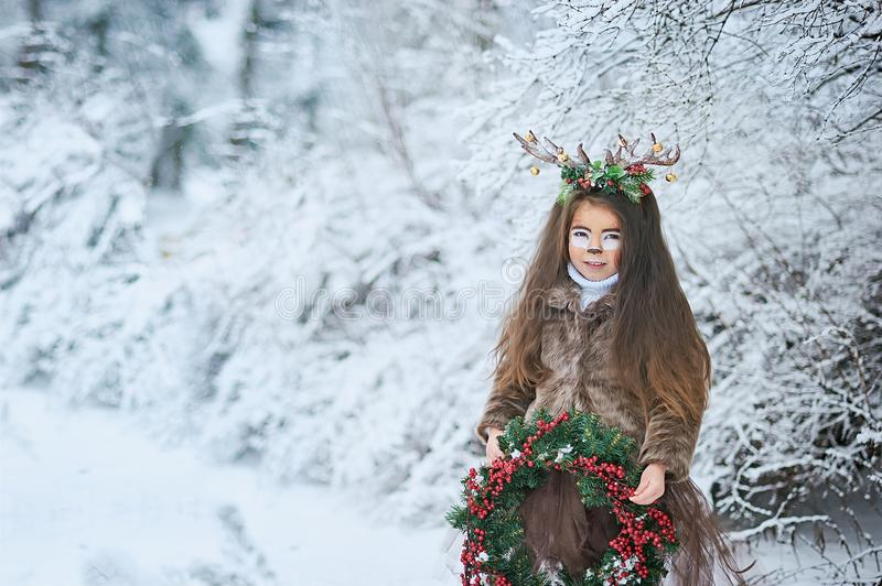 Fairy tale girl. Portrait a little girl in a deer dress with a painted face in the winter forest. Big brown antler stock image