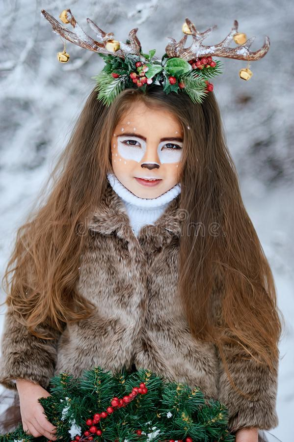 Fairy tale girl. Portrait a little girl in a deer dress with a painted face in the winter forest. Big brown antler. Fantasy girl with christmas wreath. Snowy stock photography