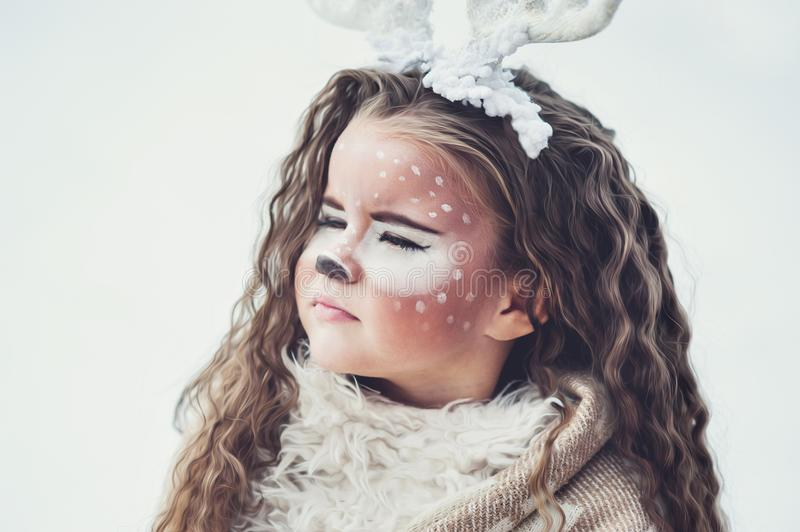 Fairy tale girl. Portrait a little girl in a deer dress with a painted face in the winter forest stock image