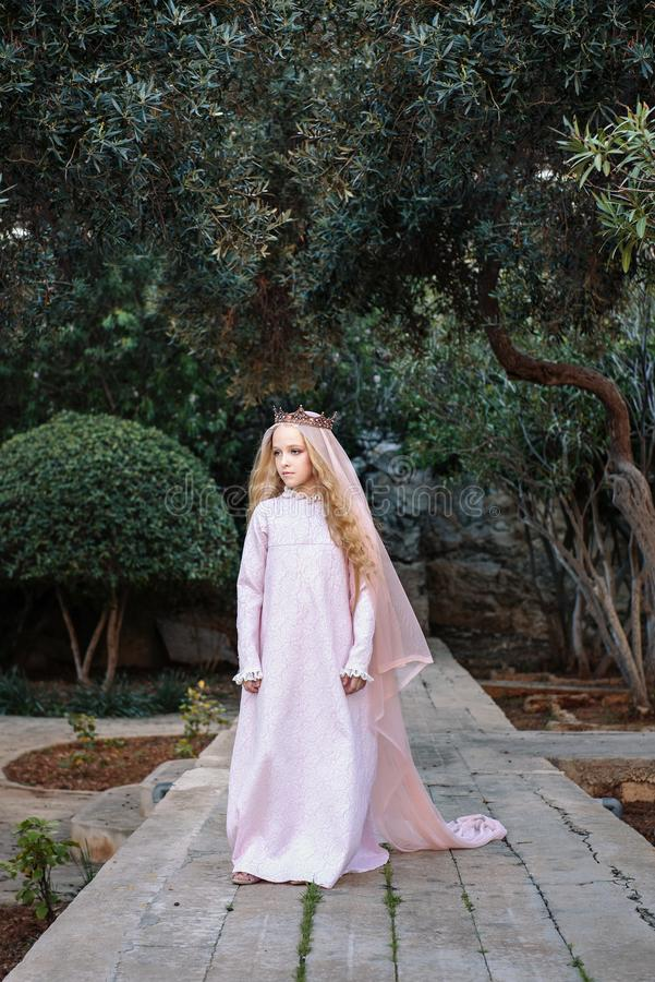 Fairy-tale kind white sorceress in a magical forest walks along the path in a dress and a crown with a veil. A fairy-tale kind white sorceress in a magical royalty free stock photos