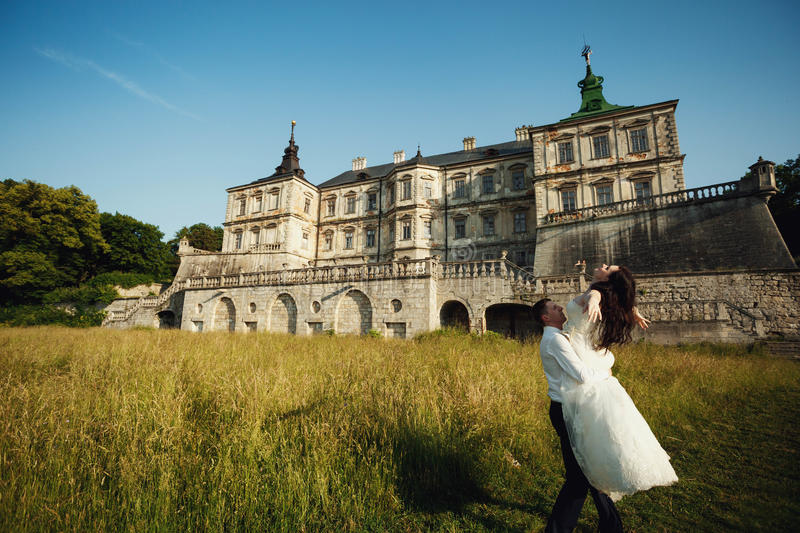 Fairy-tale wedding couple handsome groom swinging beautiful bride at sunset castle background stock photo