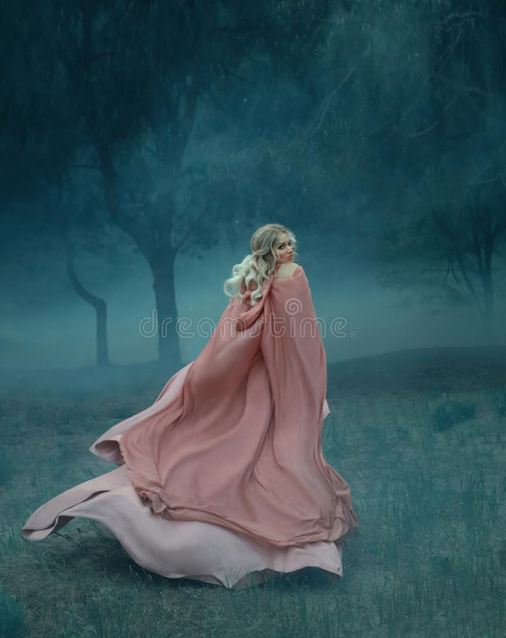 Fairy-tale witch with blond hair who runs in a dark and dense mysterious forest full of white mist, dressed in a long stock photos
