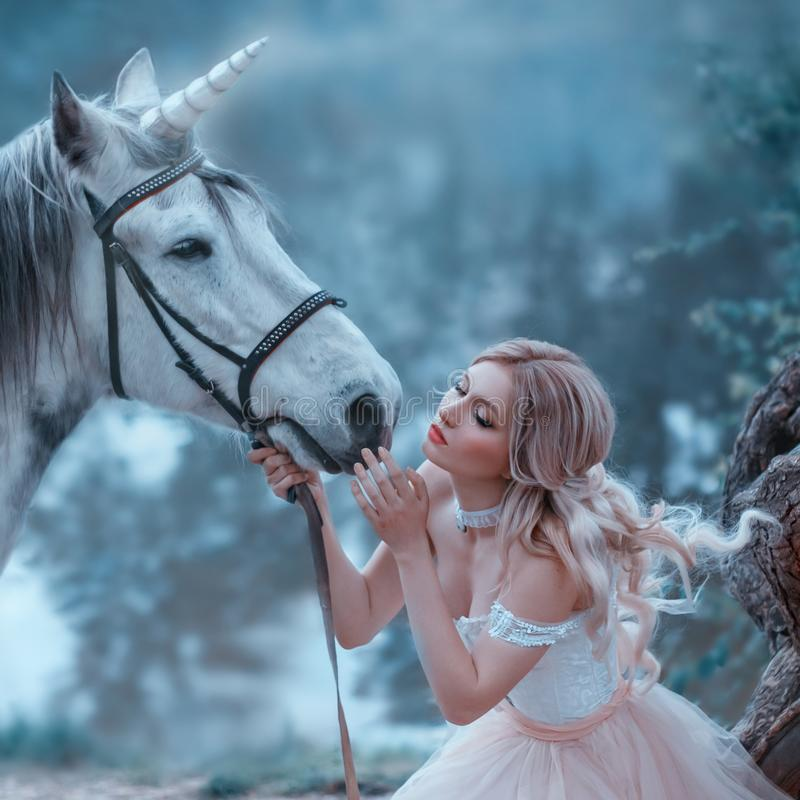 A fairy in a tender vintage dress hugs a unicorn. Fantastic magical, radiant horse. Background river and forest. Blonde stock photo