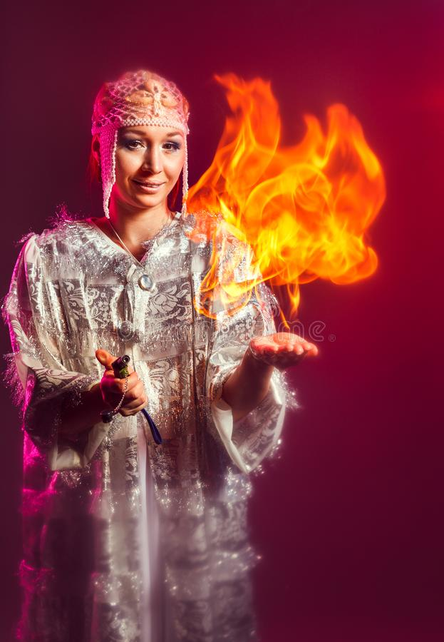 Fairy in a white festive new year costume lights a flame on her hand stock photo