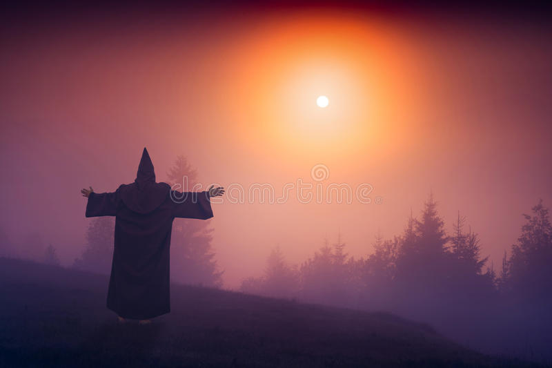 Fairy wizard in a black cassock. Standing on a hill and welcome raising sun above the foggy valley stock photos