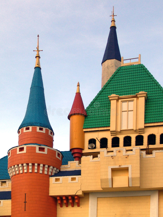 Fairytale castle soaring into blue sky. Faux-medieval castle featuring colorful rooftops soaring into blue sky stock images