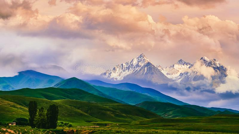 Fairytale dawn, sunset with bright multi-colored clouds, against the backdrop of a mountain range with snowy peaks and bright gree stock image