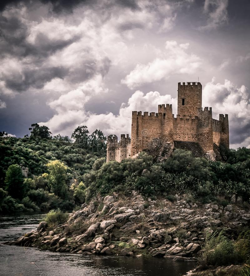 Fairytale knights templar Almoural castle on an island. Medieval Knights Templar castle on an island in the middle of a river in Portugal. Daytime image with stock images
