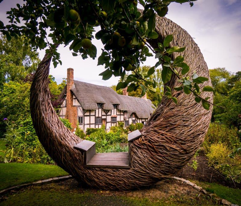Fairytale met stro bedekte dakplattelandshuisje en tuinen in Engeland royalty-vrije stock afbeelding