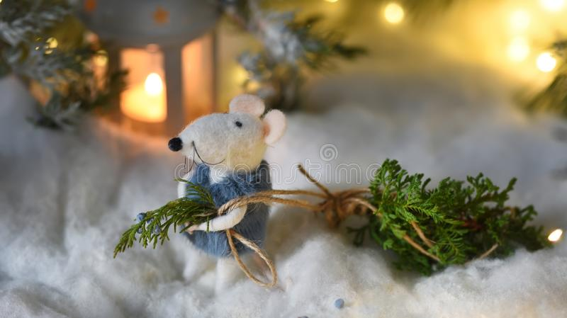 A fairytale rat in a fur coat carries a Christmas tree from a magical fairytale forest lit by lanterns. Magical New Year Christmas royalty free stock photography