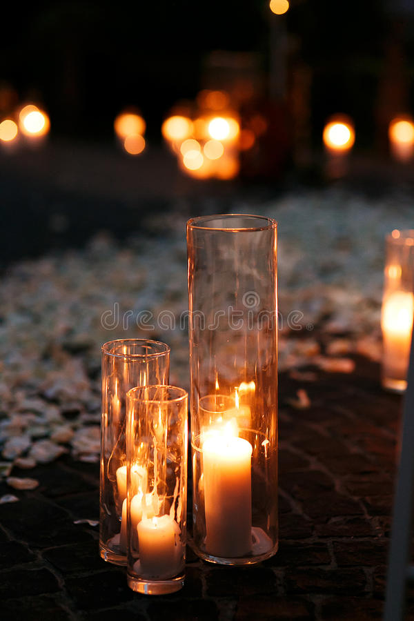 Fairytale romantic wedding aisle with white candles and petals i. N the evening stock image