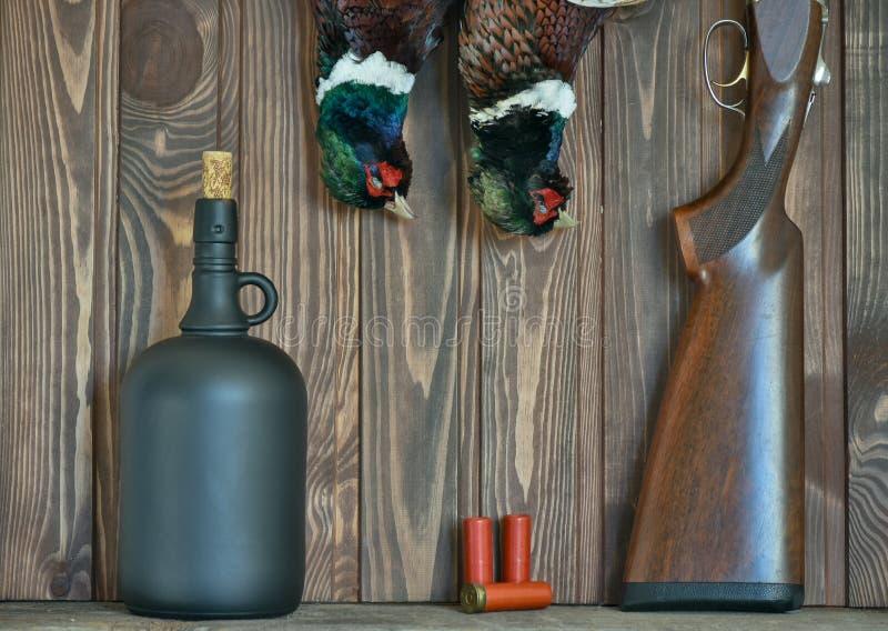 Faisans masculins, bouteille en verre, et arme à feu, sur un vieux fond en bois Saison de chasse photos libres de droits