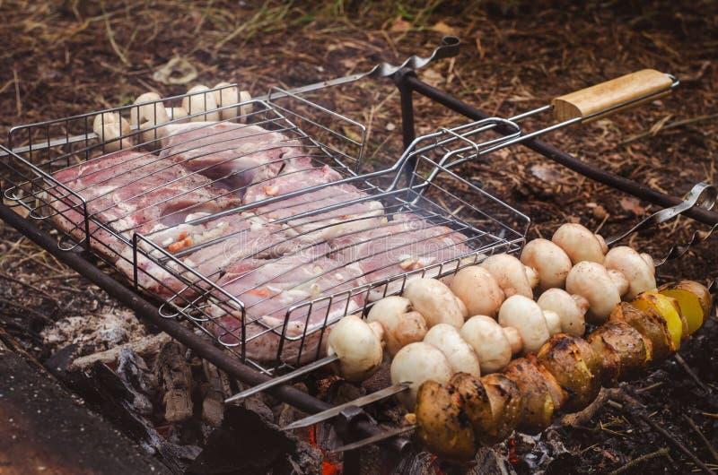 Faisant cuire des pommes de terre de champignons de bifteck sur le gril râpe image stock