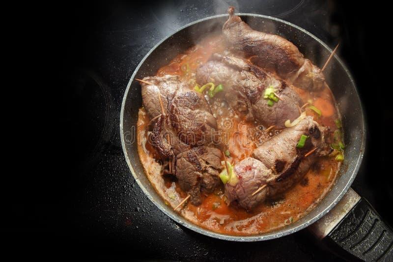 Faisant cuire des roulades de boeuf, l'Allemand a bourré des roulades de viande avec des légumes photos libres de droits