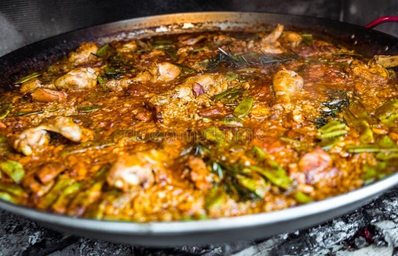 Faisant cuire et faisant une Paella espagnole traditionnelle au-dessus du feu ouvert image libre de droits