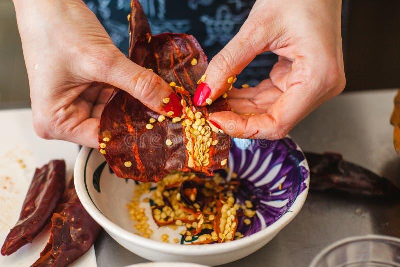 Faisant cuire l'ancho de piment, le Mexicain a séché des graines de poivre de piment image libre de droits