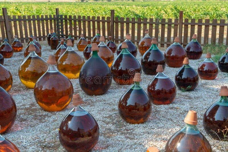 Faisant de l'extérieur doux naturel de vin blanc de liqueur de muscat de dessert dans des bouteilles antiques en verre de dame -  photographie stock libre de droits