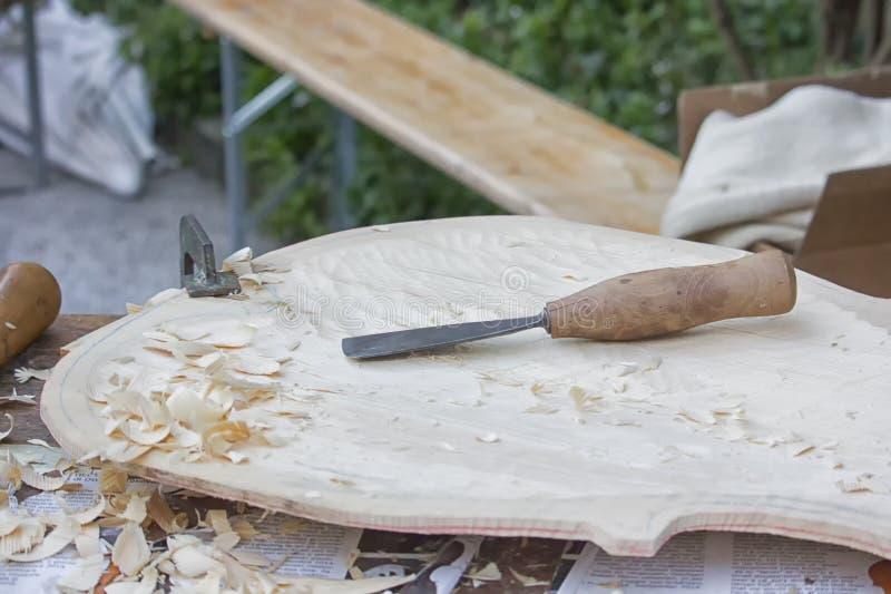 Faisant des instruments de musique en bois, découpant avec le burin images stock