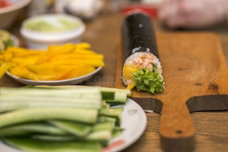 Faisant des sushi et des petits pains à la maison Plats avec des ingrédients pour les petits pains japonais traditionnels de nour photographie stock libre de droits