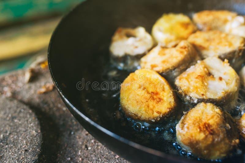Faisant frire des tranches de poissons de merluches dans la casserole dehors sur le pique-nique photos stock