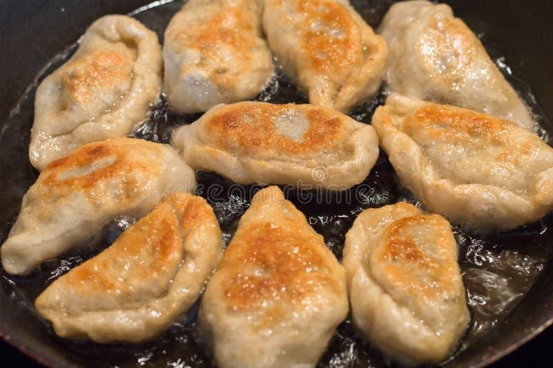 Faisant frire les boulettes frites faites maison polonaises connues sous le nom de pierogi photos stock
