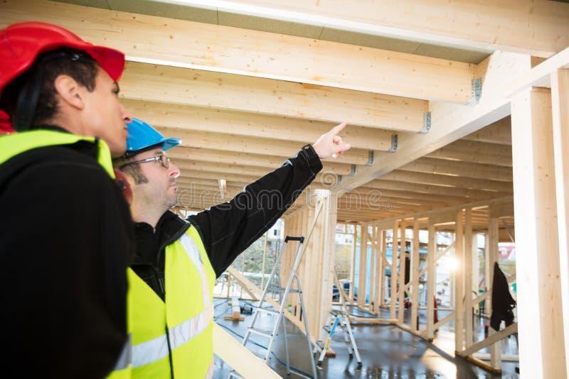 Faisceau de Pointing On Roof de charpentier tout en se tenant prêt le collègue images libres de droits