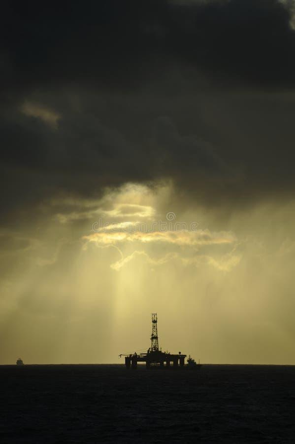 Faisceaux de lumière de Sun au-dessus de plateforme pétrolière images libres de droits