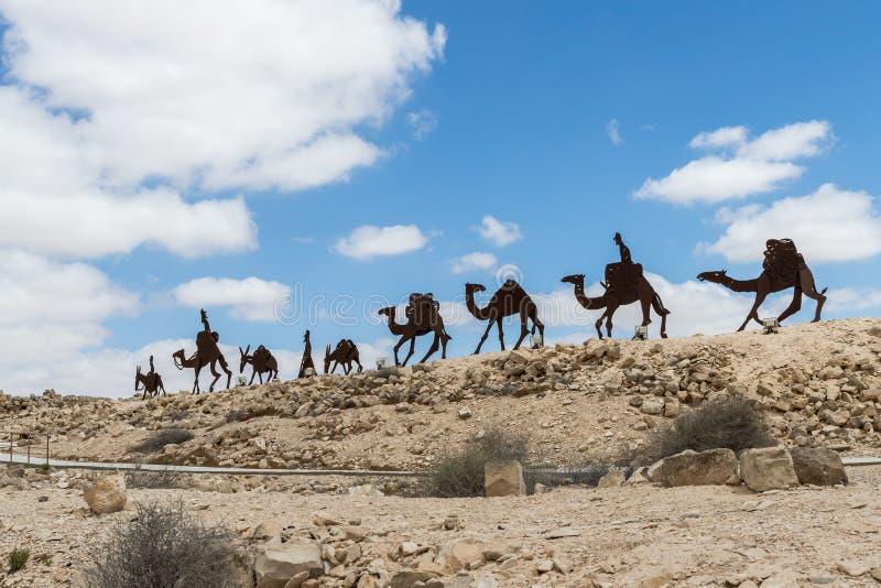 Fait des silhouettes en métal d'une caravane de marche des personnes, des ânes et des chameaux près des ruines de la ville Avdat  photos stock