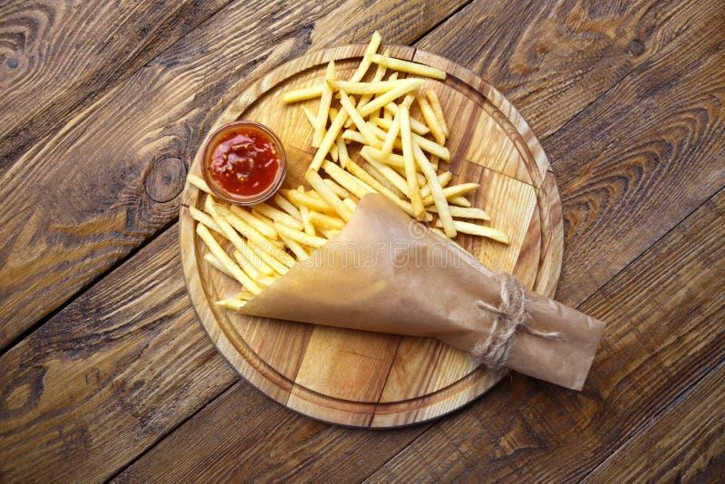 Fait frire des pommes chips a enveloppé le traiteur sur le bois, vue supérieure photo stock