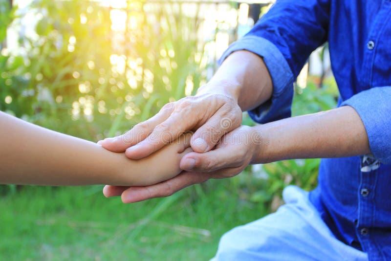 Faites attention, homme supérieur tenant des mains de fille de petit enfant sur le fond vert naturel photos stock