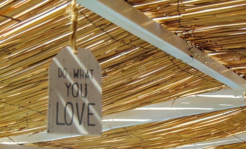 Faites ce que vous aimez la citation inspir?e accrochant sur le toit de paille photos stock