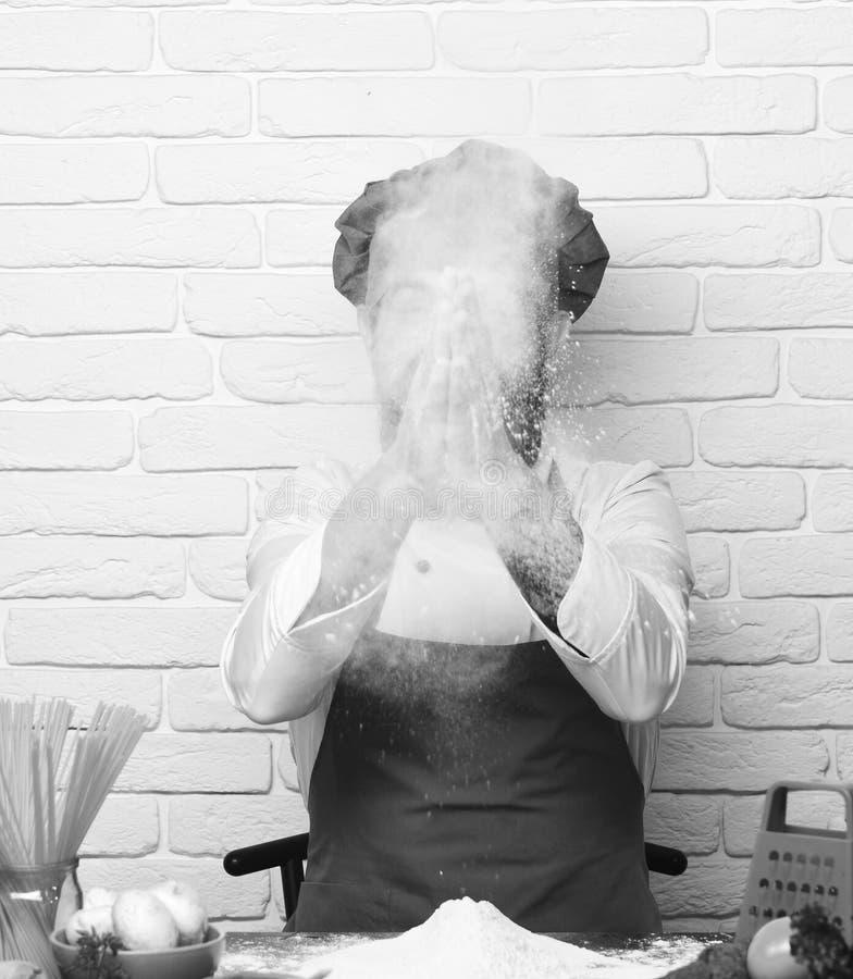 Faites cuire avec le visage caché dans l'uniforme de Bourgogne se repose par la table photos libres de droits