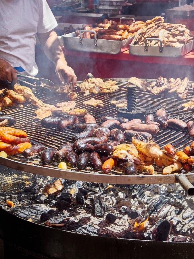 Faites cuire faire cuire les saucisses, le lard et le poulet sur un BBQ de charbon de bois photos stock