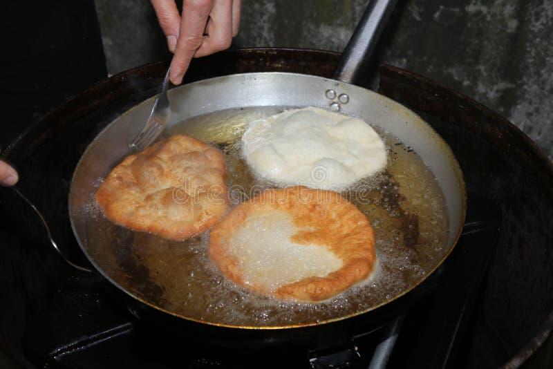 Faites cuire les mains tout en faisant cuire les beignets frits plongés dans l'oi de ébullition images libres de droits