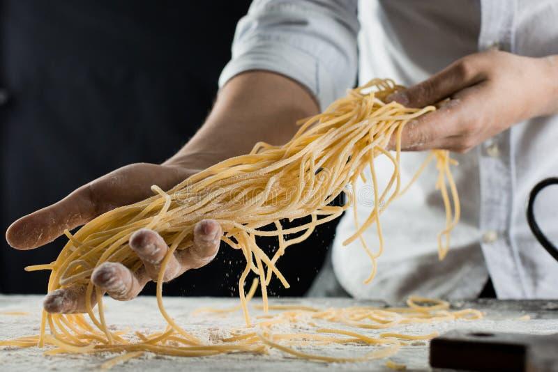 Faites cuire tenir les spaghetti fraîchement cuits dans la cuisine photographie stock libre de droits