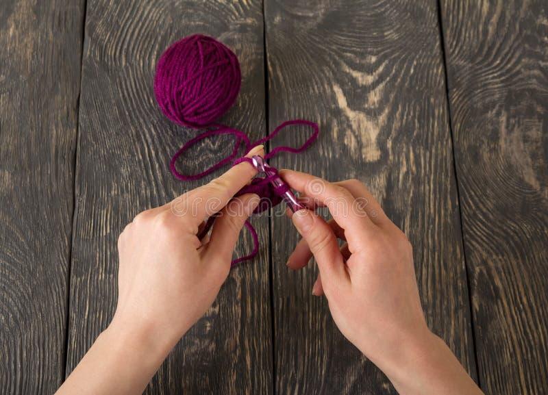 Faites du crochet, artisane de main au travail, sur la table en bois foncée photo stock