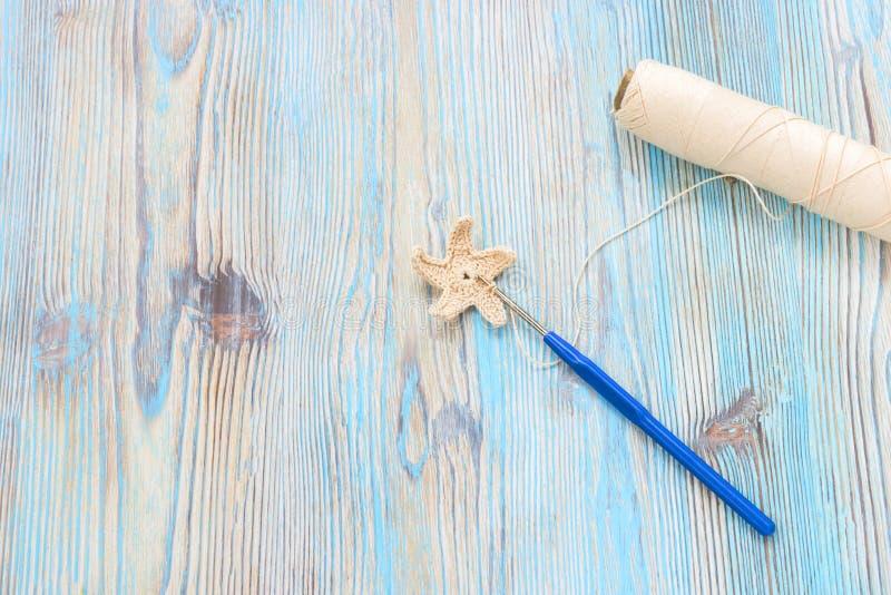Faites du crochet l'étoile faite main, la boule beige de fils de coton et le crochet en métal de crochet sur la table en bois photographie stock