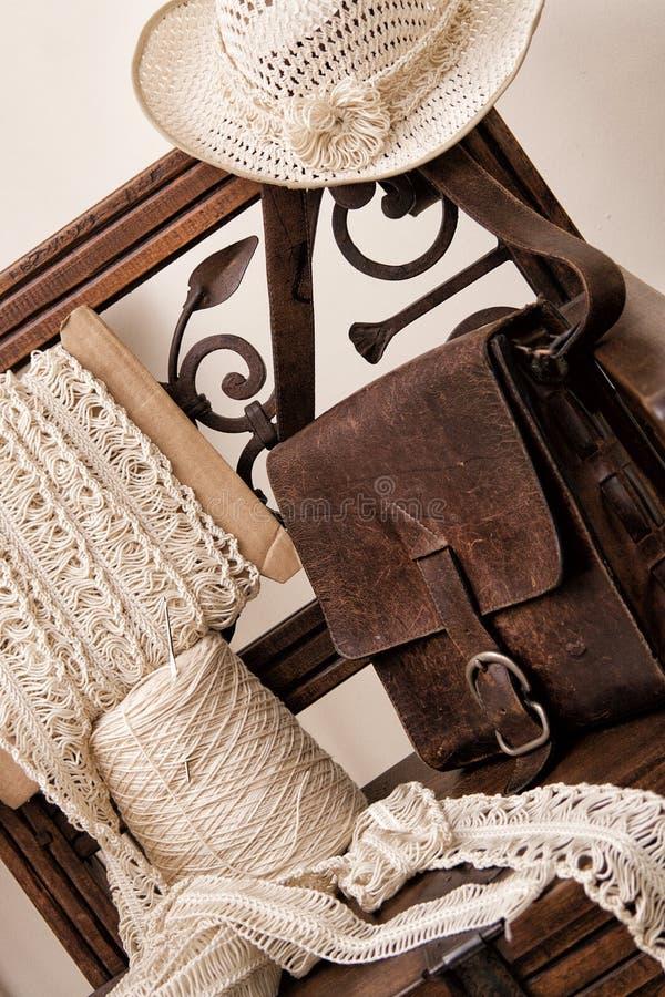 Faites du crochet les outils accompagnés du sac en cuir élégant sur la chaise en bois photo libre de droits