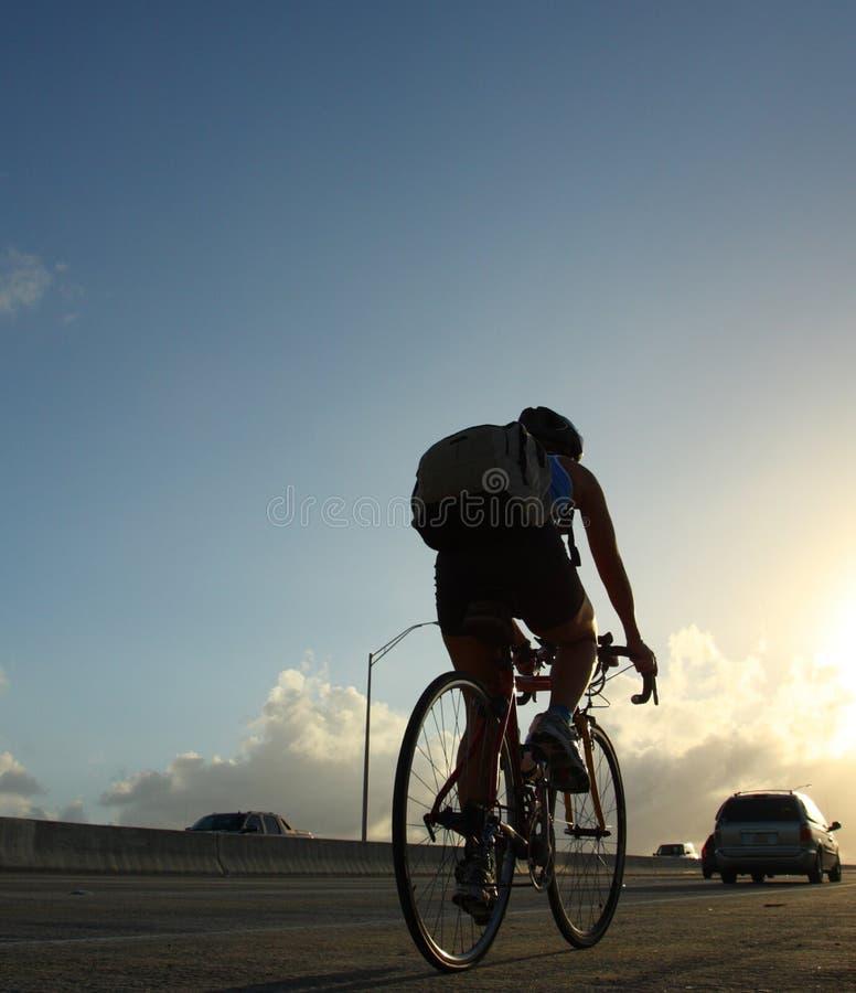 Faites du vélo l'équitation dans le coucher du soleil photo stock