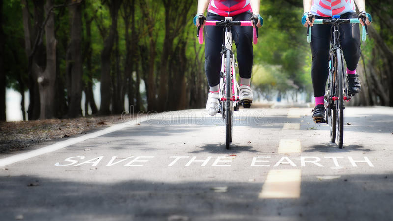 Faites du vélo la ruelle et les mots des économies la terre sur la route image stock
