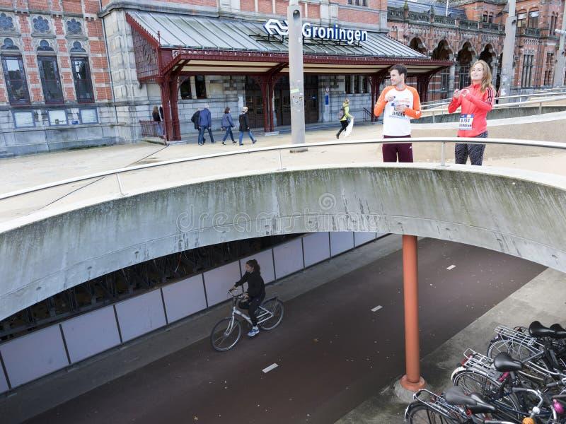 Faites du vélo sur la voie de bicyclette sous la place devant la gare ferroviaire Groningue en Hollandes images stock