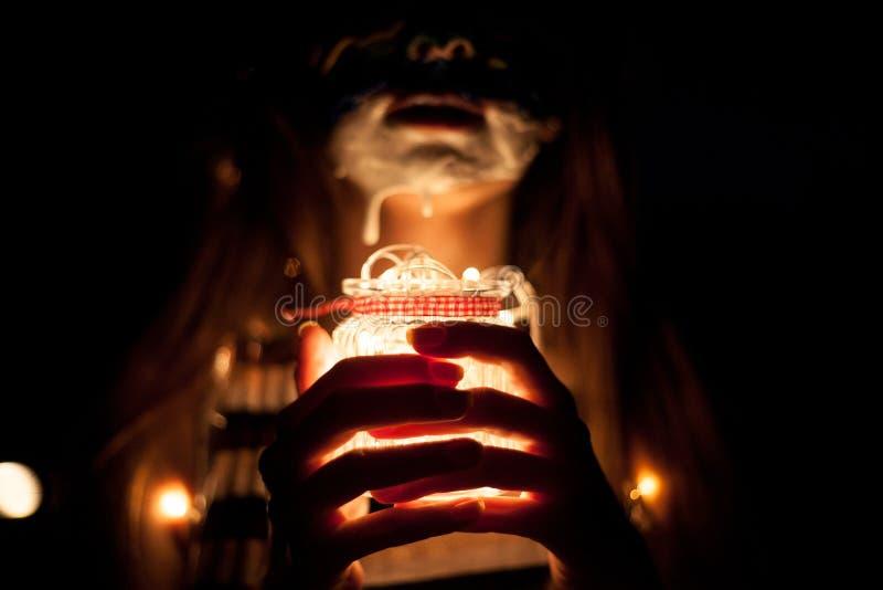 Faites face à la fille d'art avec un pot en verre dans des mains avec des lumières la nuit images stock