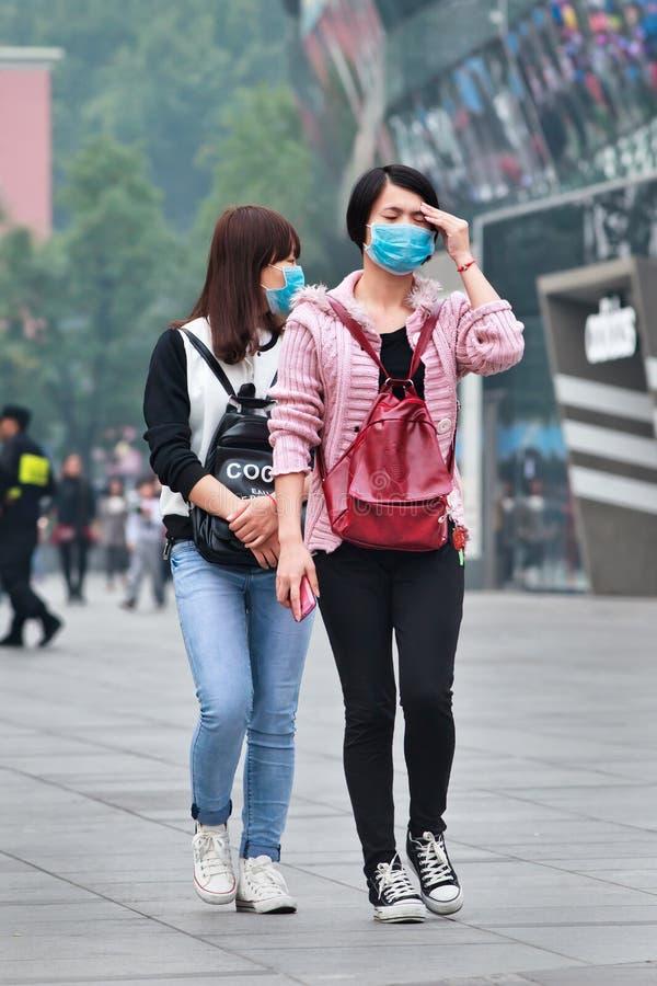 Faites face à la fille masquée obtient étourdi du brouillard enfumé, Pékin, Chine image libre de droits