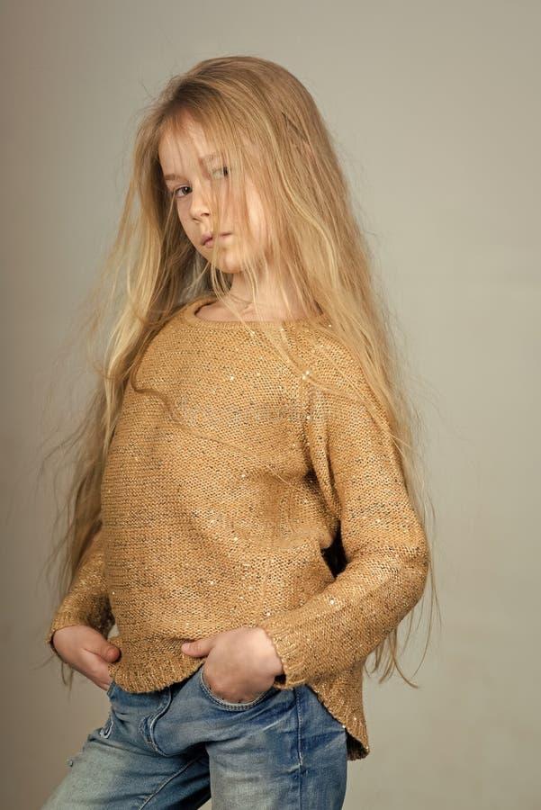 Faites face à la petite fille ou à l'enfant de mode en votre site Web Façonnez à port d'enfant de petite fille les jeans des vête photos stock