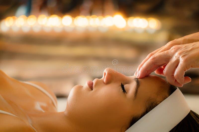 Faites face au tir de la femme ayant le massage ayurvedic à la basse lumière de bougie image stock