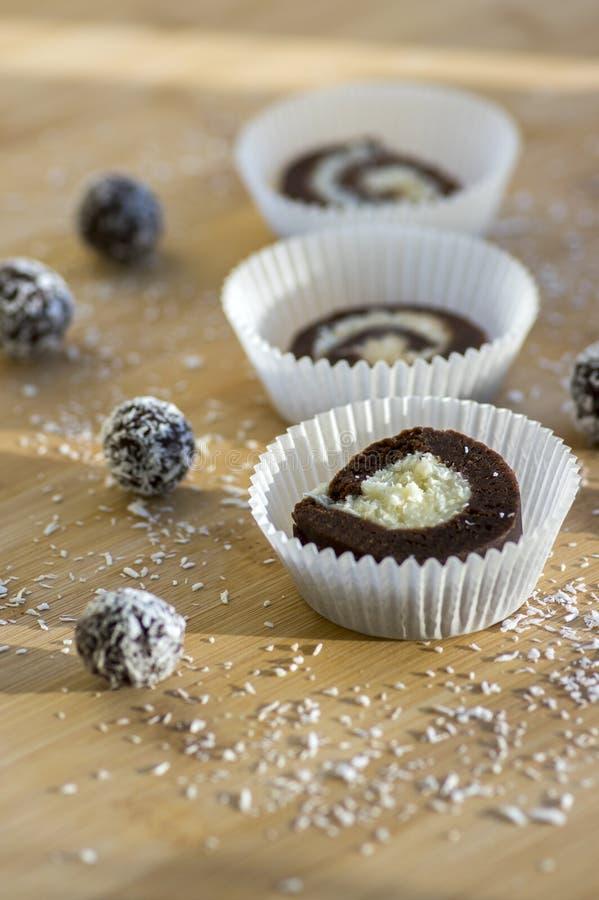 Faites la fête les biscuits non cuits de noix de coco d'anad de café en petits gâteaux de papier sur la table en bambou en bois,  photos libres de droits
