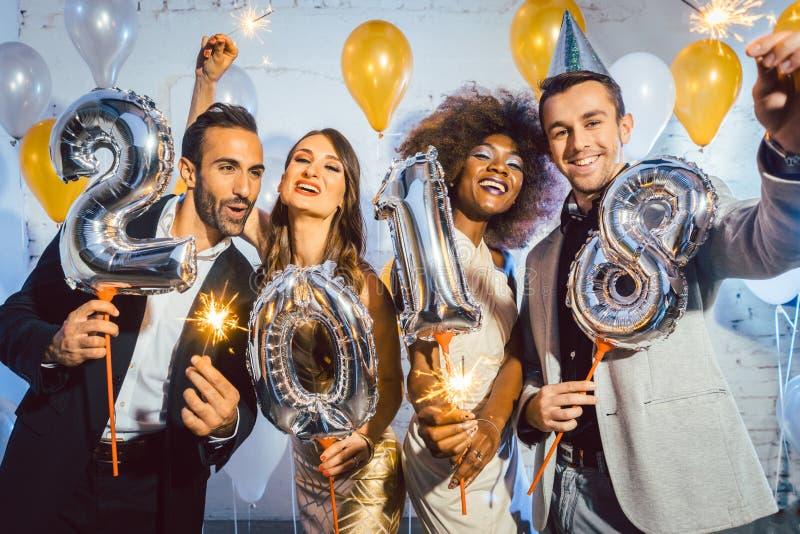 Faites la fête les femmes et les hommes de personnes célébrant la veille de nouvelles années 2018 image libre de droits