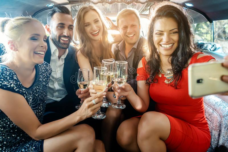 Faites la fête les personnes dans une limousine avec des boissons prenant un selfie avec le téléphone photos stock