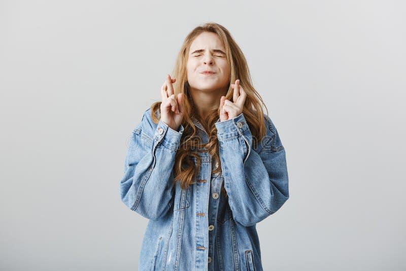 Faites mes rêves venir vrai, svp Portrait de studio d'amie européenne blonde belle dans la veste élégante de denim images stock