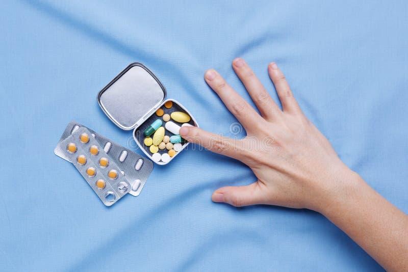 Faites souffrir de la maladie avec la main essayant de prendre des pilules photographie stock